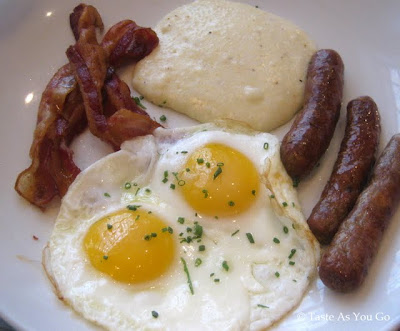 Aged Cheddar Grits, Fried Eggs, Smoked Bacon, and Maple Sausage at Punch Restaurant in New York, NY - Photo by Taste As You Go