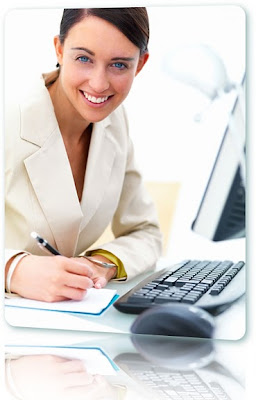 Woman in a white suit using a computer while writing in a notepad.