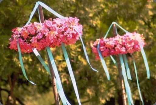 2-wreaths-covered-with-pink-flowers-are-suspended-from-a-wooden-pole-Françoise-Weeks