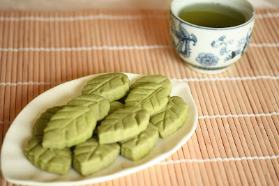 photo of a plate of Matcha Green tea shortbread leaves with a mug of tea in the background