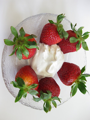 overhead photo of a bowl of Strawberries with fresh whipped cream
