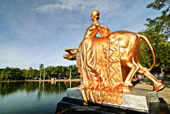 Woman with buffalo sculpture on the right side of the lagoon.