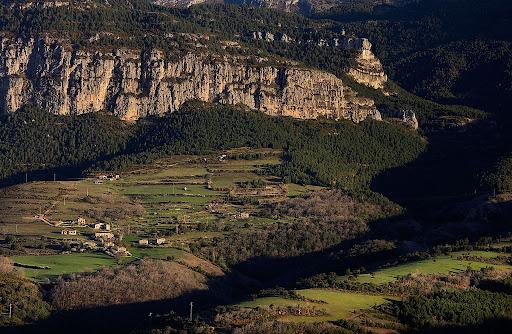 El poblet de Canalda i, darrera, la roca de Canalda, vessant sud de la serra de Querol, port del Comte, Odn, Solsons, Lleida