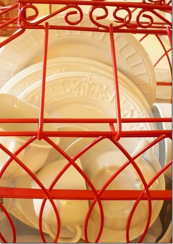 white dishes inside a red birdcage