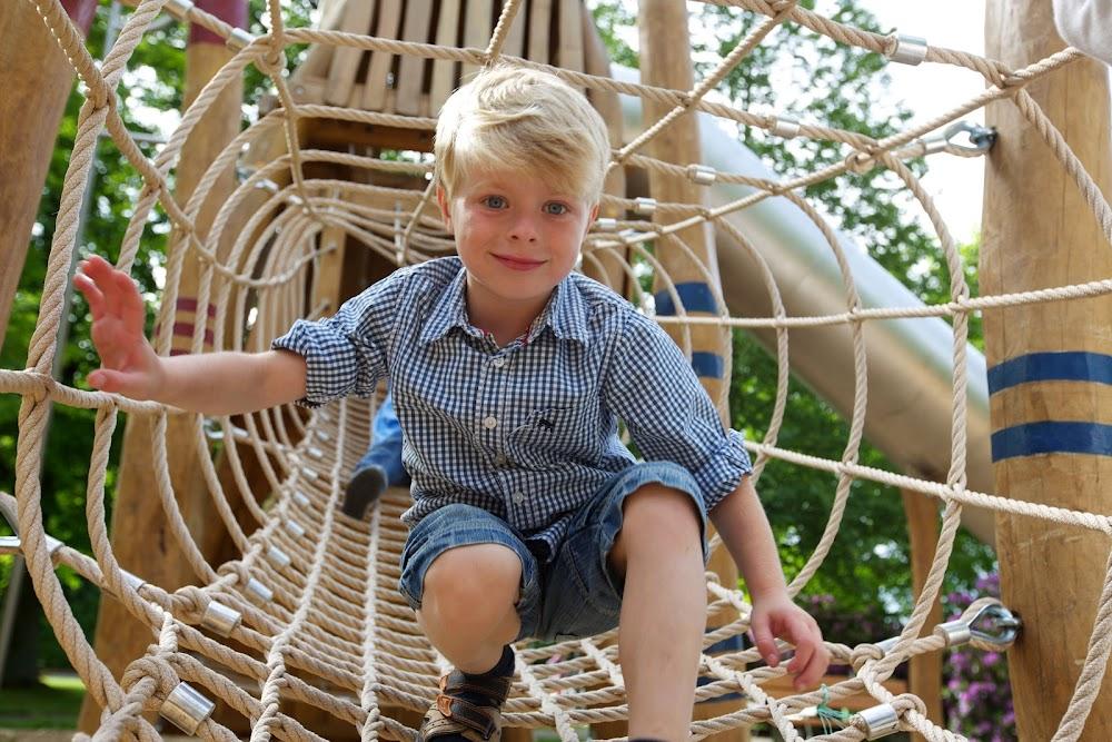 Du siehst einen kleinen blonden Jungen, der durch das Seilenetz klettert.