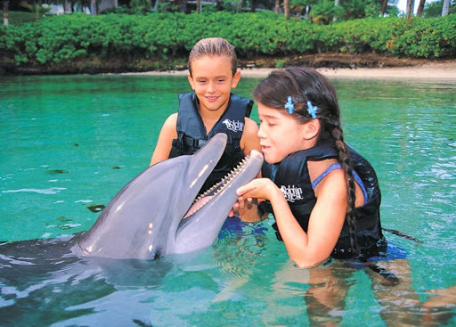 Norwegian-Cruise-Line-Splash-Academy-dolphin-girl - Children can learn all about dolphins and nuzzle with one up close through Splash Academy on your Norwegian cruise ship.