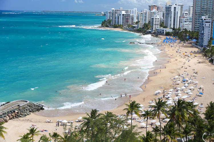 Visitors flock to Isla Verde Beach in Puerto Rico.