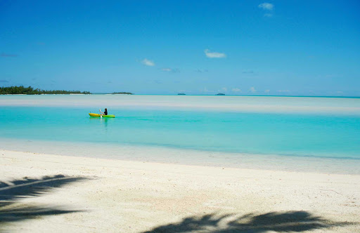 kayak-lagoon-cook-islands - A lone paddler in Akitua Lagoon, on Aitutaki, the Cook Islands.