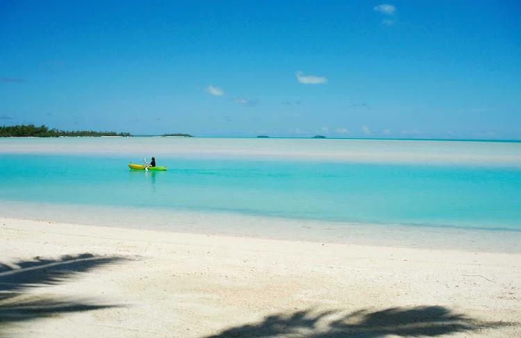 A lone paddler in Akitua Lagoon, on Aitutaki, the Cook Islands.