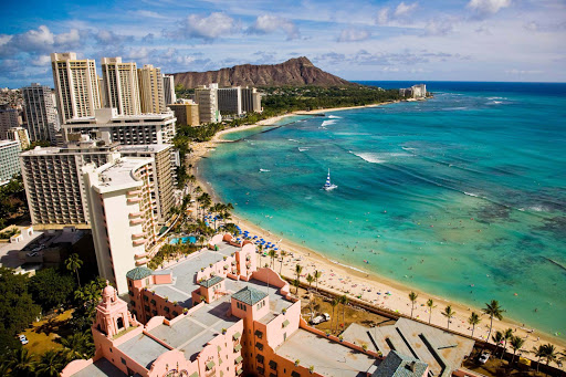 A wide shot of Waikiki Beach in Honolulu with Diamond Head in the distance.