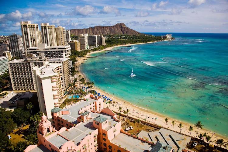 A wide shot of Waikiki Beach in Honolulu with Diamond Head in the distance.
