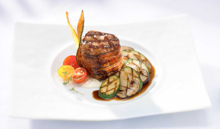 Blu Restaurant's charred grilled veal loin served with sweet cherry tomatoes, sliced zucchini and drizzled with a rich jus is just one of the appetizing main courses served during your Celebrity Cruises voyage.