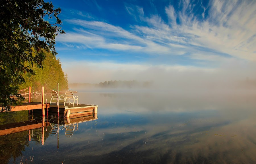 Early Morning Greeting by Roberta Janik - Landscapes Waterscapes ( morning mist, muskokas, fog, sunrise over lake, lake, reflection in lake, clouds reflected in lake, dock, mist )