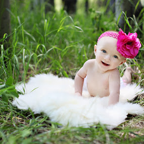 Baby on fur in grass by Kristin Cheatwood - Babies & Children Babies ( grass, happy, fur, baby, bow, sun valley )