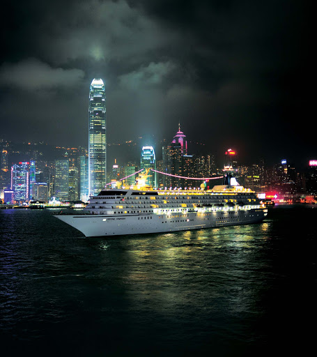 Crystal Symphony glows as it glides through the port of Hong Kong on an evening sojourn.