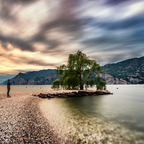 Waiting for a new beginning by Mattia Bonavida - Landscapes Waterscapes ( exposure, clouds, water, garda, colors, tourism, lake, beach, landscape, long, people, shadows, mountains, sky, sunset, trees, stones, rocks, italy )