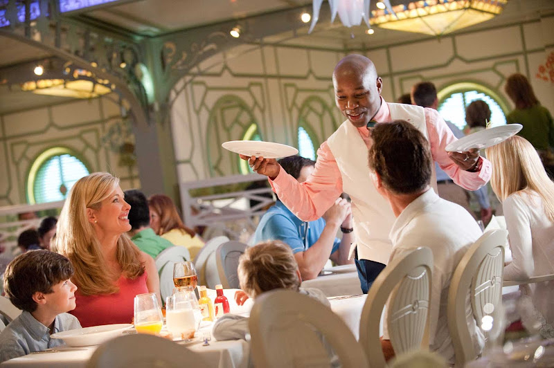 A waiter in Enchanted Garden on Disney Dream. Tips for wait staff are automatically added to your shipboard account.