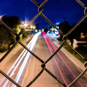 A World Apart by Will Ballew - City,  Street & Park  Street Scenes ( lights, fence, traffic, billings, mt, cars, street, light trails, night, chain link )