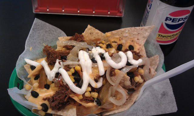 Nachos with shredded beef, black beans, corn, cheese, grilled onions, jalapenos, & sour cream!