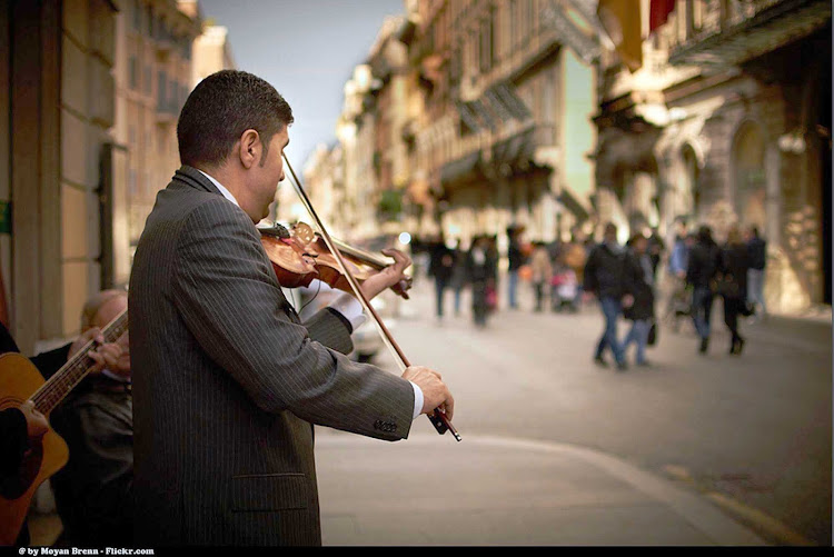 A pinstriped violinist on Via del Corso in Rome.