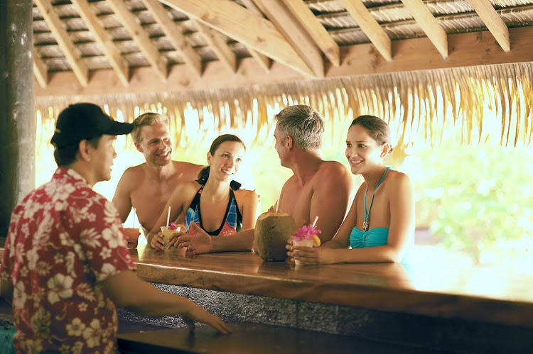 Paul Gauguin guests relax at the bar on the beach at Motu Mahana, a tiny island off Taha'a in the Society Islands.