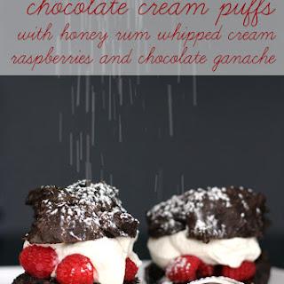 Chocolate Cream Puffs with Honey Rum Whipped Cream, Raspberries and Chocolate Ganache.